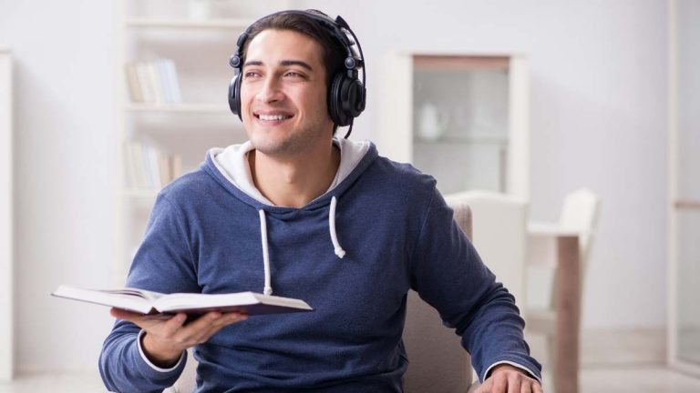 A man is listening to an audiobook using headphones.